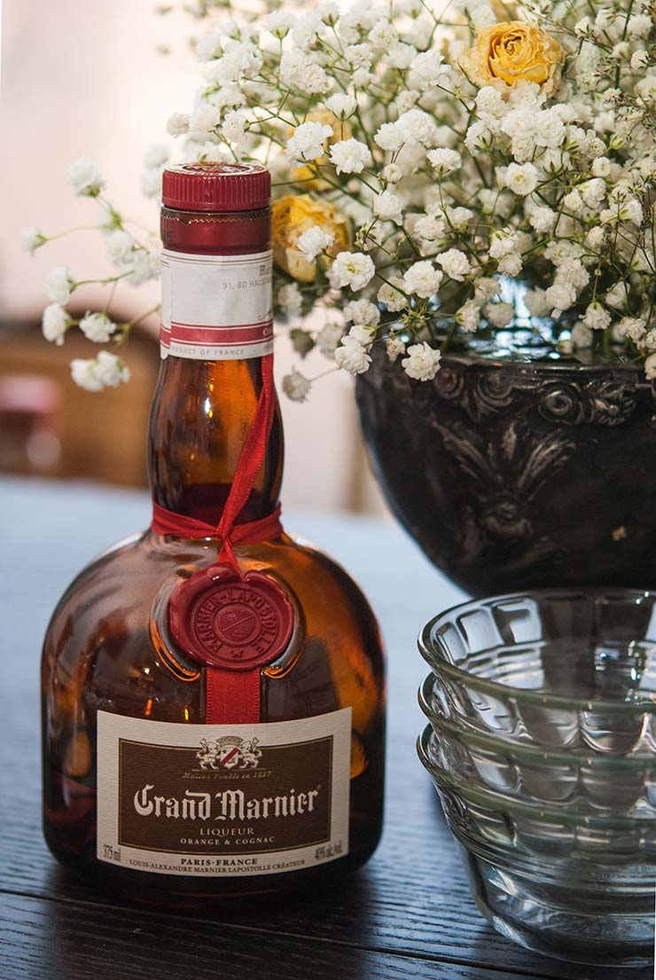 A bottle of Grand Marnier on a black table next to 3 stacked ramekins and a flower an arrangement of baby's breath and roses