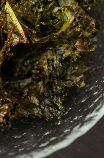 A glass bowl of kale chips.
