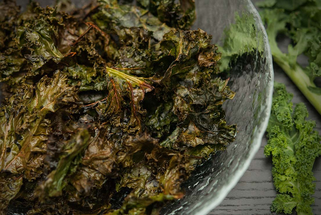 A bowl of kale chips on a black table.