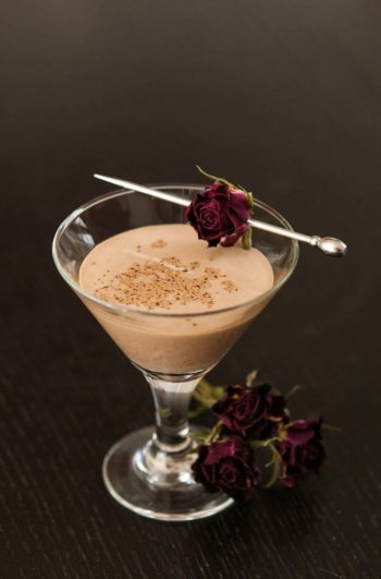 A small glass of Mexican chocolate liqueur sprinkled with cinnamon on a black table with small roses for garnish.