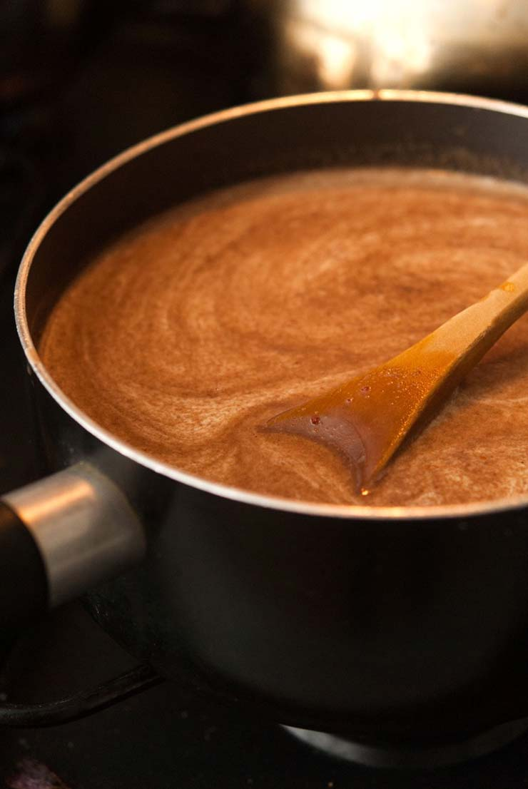 A pot on a stove with a spiral of spices in Mexican cream chocolate liqueur.