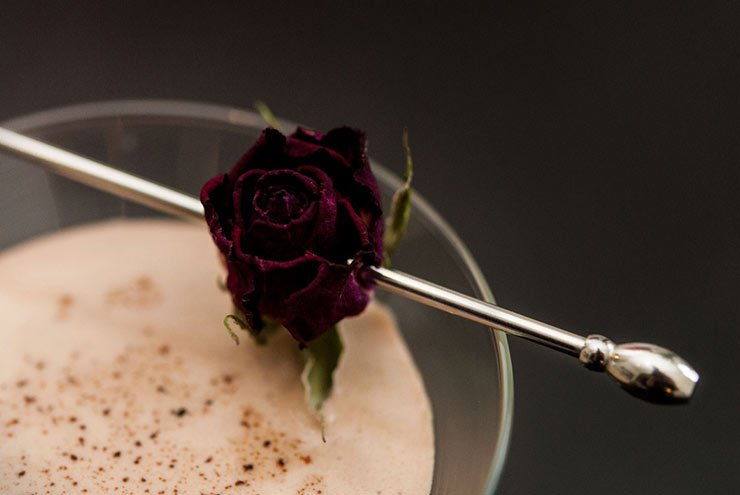 A closeup of a tiny rose pierced with a cocktail pin, sitting on the edge of a Mexican Liqueur cocktail.