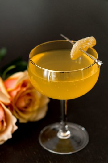 A cocktail on a black table garnished with ginger beside 2 roses.