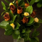 """A """"bouquet"""" of bacon roses in a vase with leaves and yellow spray roses."""