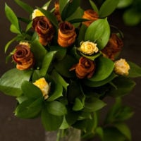 "A ""bouquet"" of bacon roses in a vase with leaves and yellow spray roses."