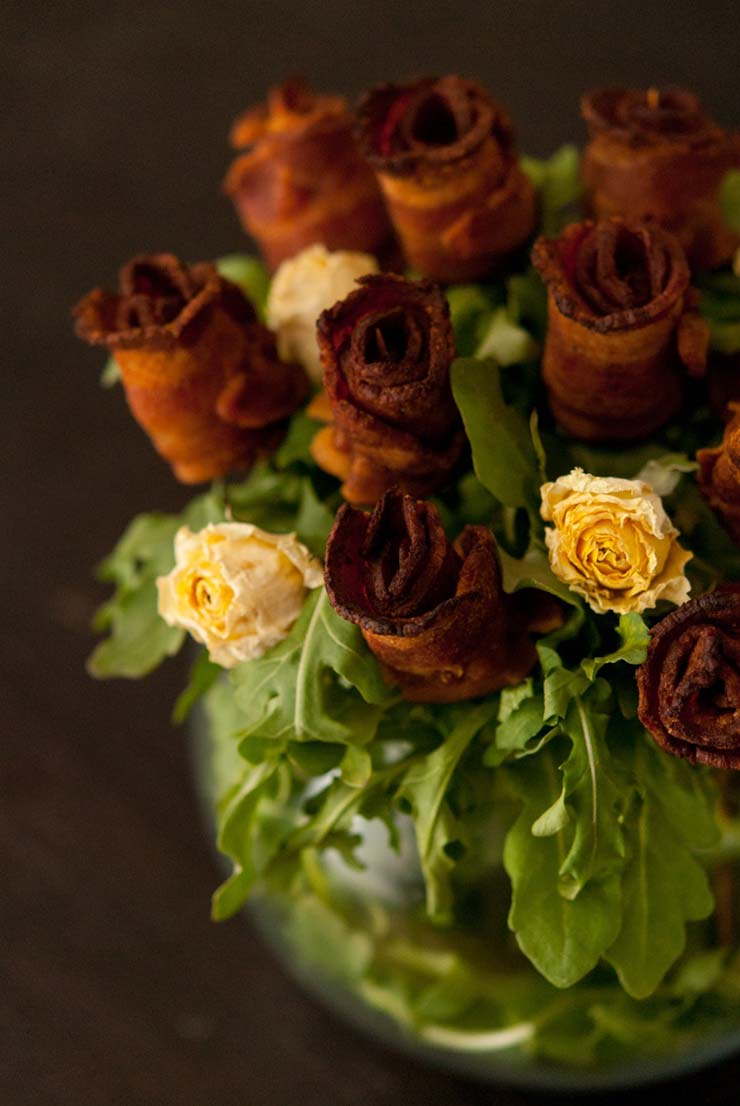 A bacon rose bouquet with yellow roses in a bowl with arugula on a dark table.