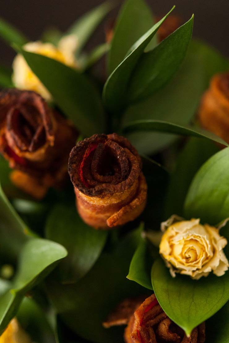 A bacon rose next to yellow roses in a bouquet.