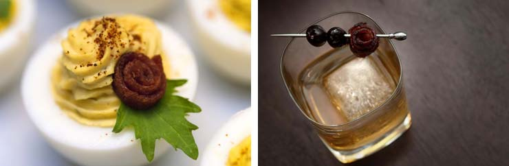 A deviled egg garnished with a bacon rose next to a whisky cocktail garnished with a bacon rose and 2 olives on a dark table.