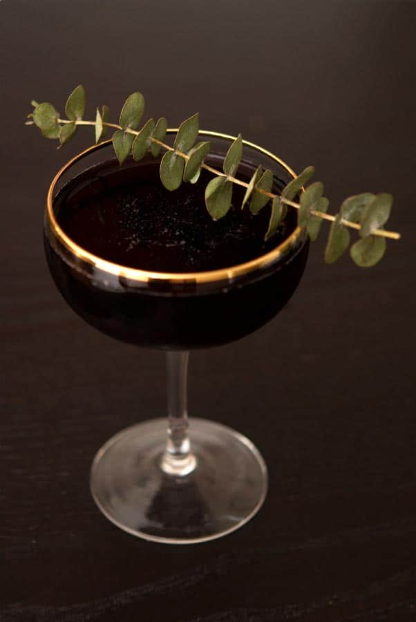 A cocktail garnished with eucalyptus on a dark table.