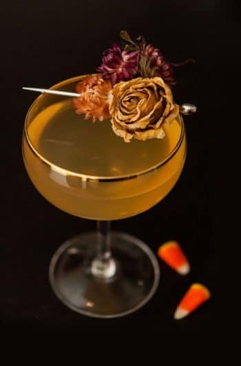 A cocktail on a table garnished with dry flowers with 3 candy corns at its base.