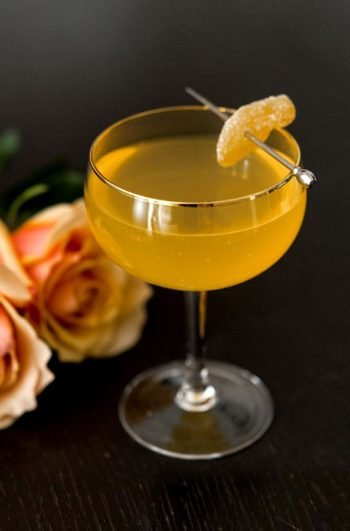 A cocktail garnished with a small slice of ginger.