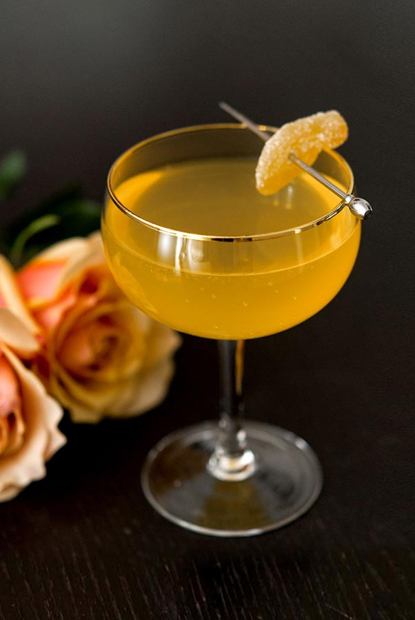 A cocktail garnished with a small slice of ginger on a dark table beside 2 roses.