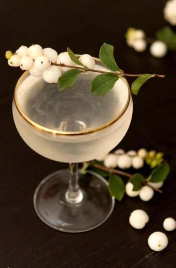 A cocktail ganrished with ghostberries on a black table.