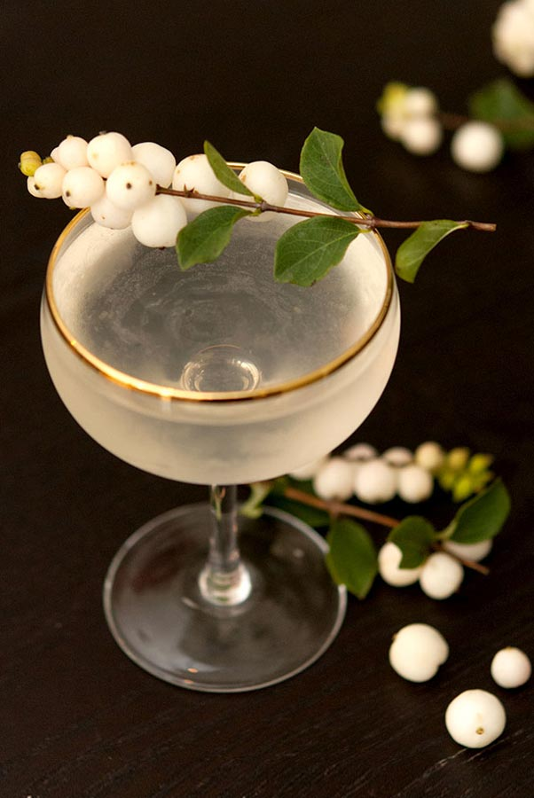 A cocktail garnished with ghost berries on a black table with berries at its base, and in the background.
