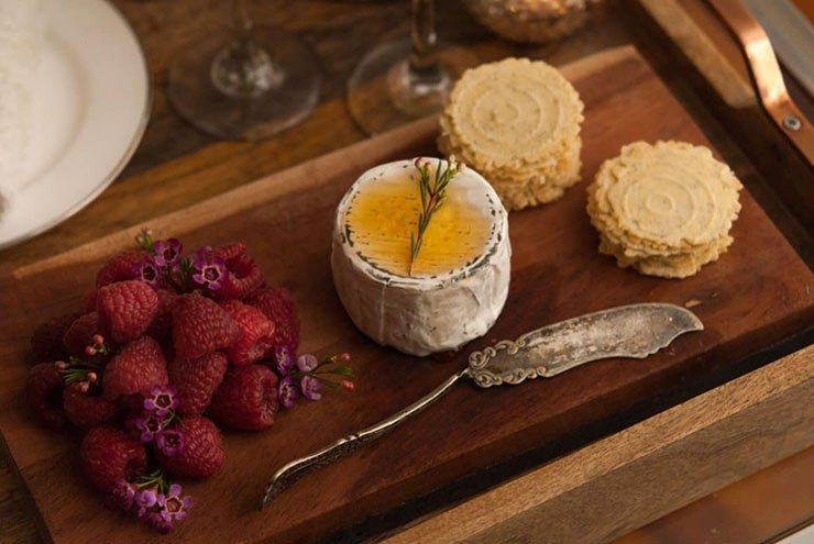 A cheeseboard with raspberries, cheese, garnished with honey and a sprig of flowers, an antique cheese knife and crackers.