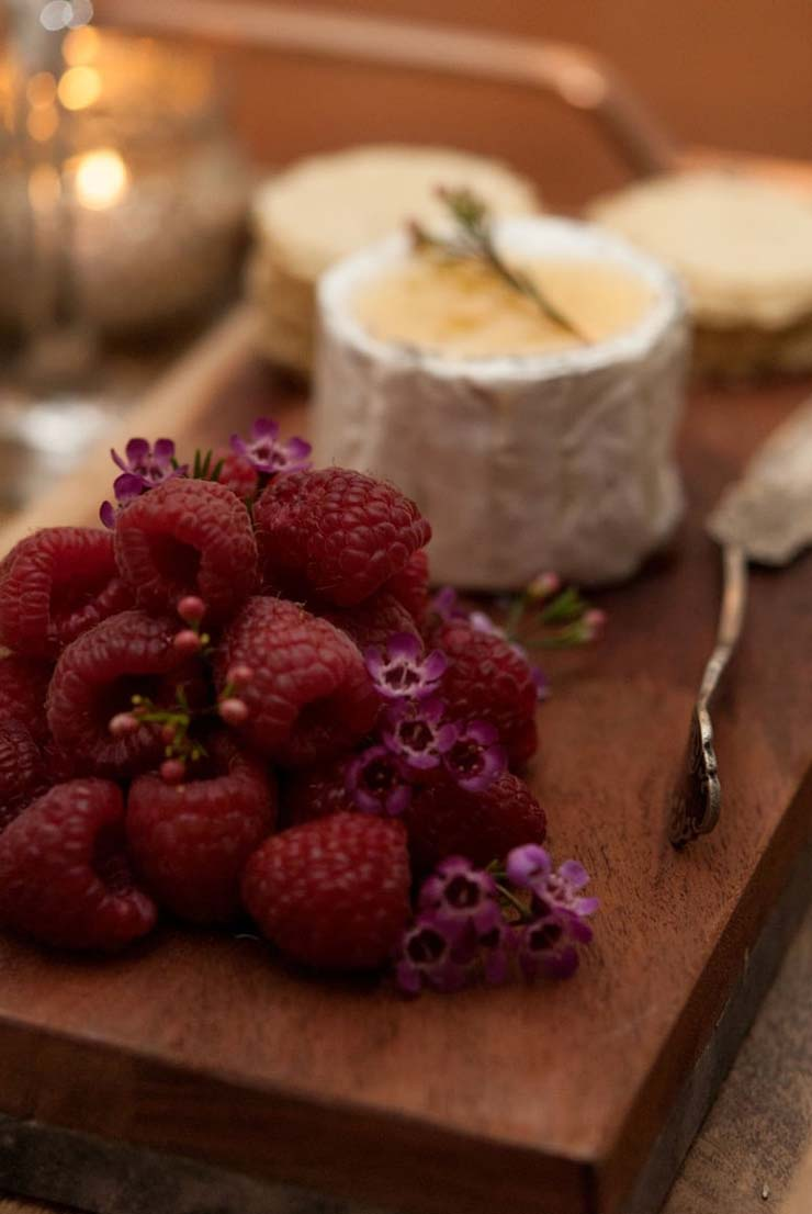 Raspberries stacked on a wooden cheeseboard, garnished with little flowers, beside cheese and a cheese knife.