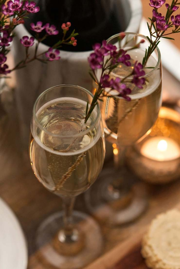 2 full champagne glasses, garnished with flowers next to a small candle on a wooden tray, next to a champagne bottle.