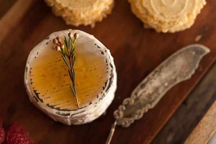 A cheese, drizzled in honey and garnished with a small flower beside an antique cheese knife and a few stacked crackers.