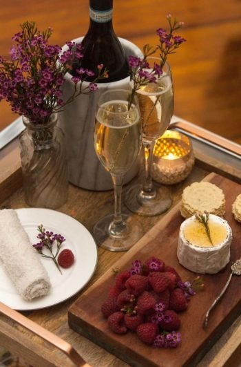 A wooden tray holding 2 champagne glasses garnished with flowers, a dark wooden cheese board holding raspberries, cheese and crackers, a plate with a small rolled towel, a glass vase with flowers and a marble wine holder, holding a Champagne bottle.