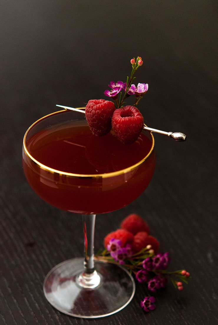 A cocktail on a black table garnished with raspberries and small flowers.
