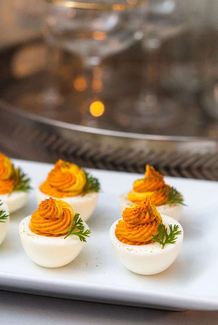 5 multi-colored deviled eggs on a white plate in front of a silver tray holding glasses.
