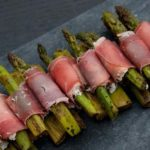 A pile of prosciutto-wrapped asparagus on a marble plate in a row.