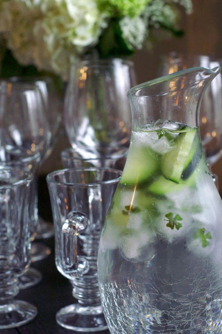 A bottle of water with cucumbers and ice with basil shamrocks inside, in front of a few scattered glasses and white flowers on a table.