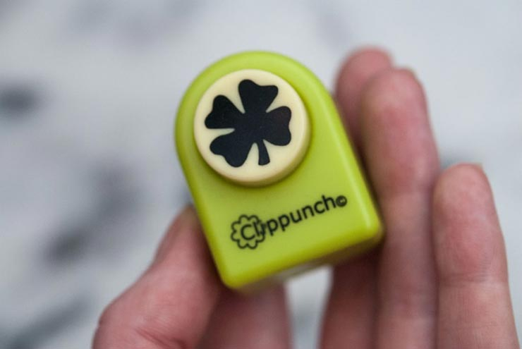 A hand holding a shamrock hole puncher over a white background.