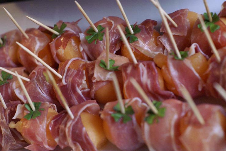 A closeup of prosciutto-wrapped melon with little basil shamrocks stuck into them with toothpicks.