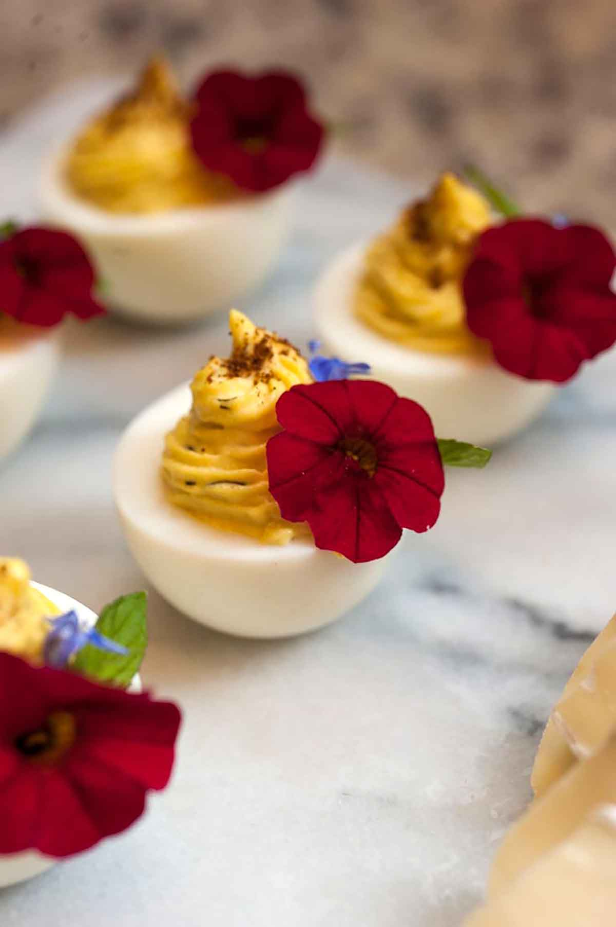 5 deviled eggs, garnished with red flowers on a marble board.