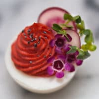 A deviled egg with red filling on a marble plate, garnished with small flowers, thyme and 2 slices of radish.