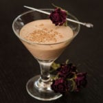 A smal cocktail, garnished with a single rose, with roses at its base.