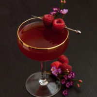 A cocktail on a table garnished with raspberries and small flowers, with small flowers and berries at its base.