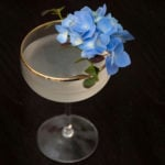 A cocktail on a table, garnished with blue flowers and a little greenery.
