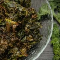 A glass bowl of kale chips on a table beside a few fresh leaves of kale.