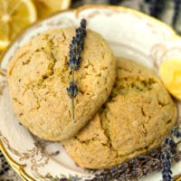 Two scones on plates with gold edges with fresh lavender placed on top, beside 2 cut lemons and a bunch of fresh lavender.