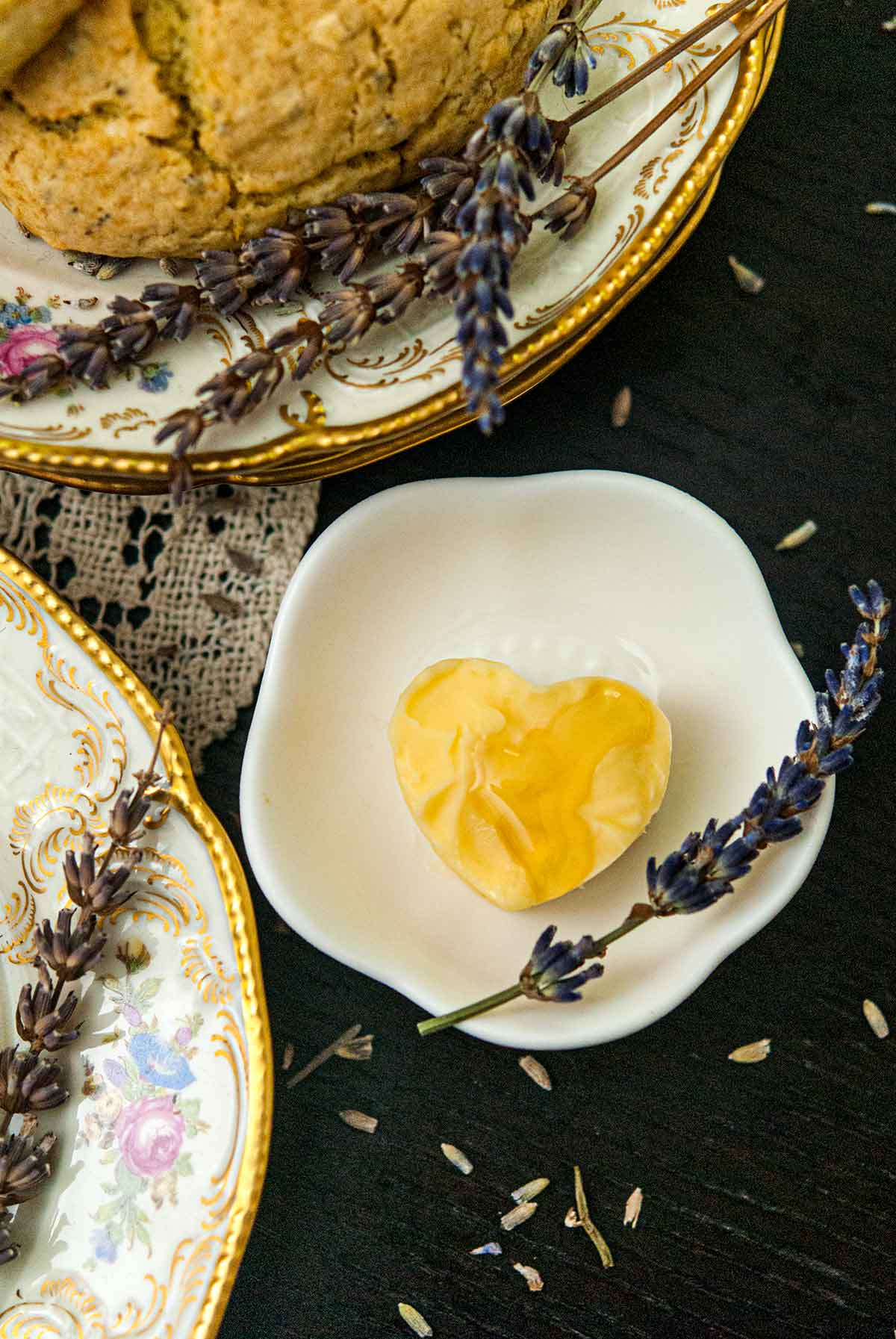 A small bowl with butter in the shape of a heart, garnished with honey and a sprig of lavender besides plates with lavender.