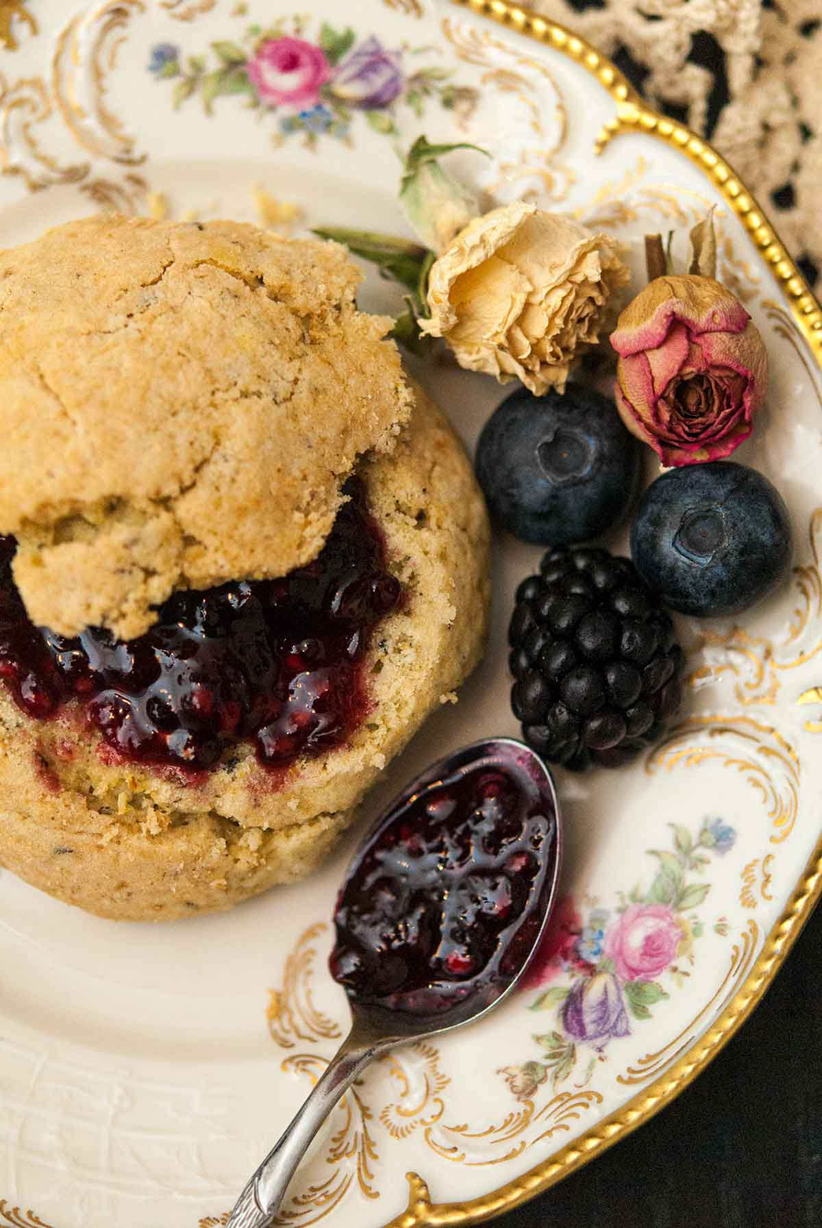 A scone with jam on a decorative plate next to a spoon with jam, a few berries and a few dry roses.