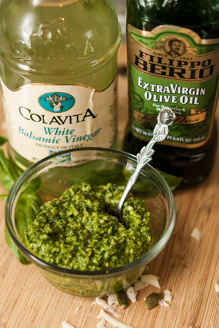 A small bowl of pesto on a wooden board in front of a bottle of balsamic vinegar and olive oil.