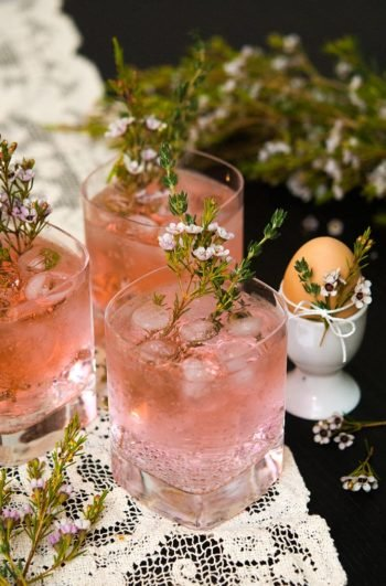 3 pink gin and tonic cocktails on a lace table cloth garnished with and surrounded by floral greenery and thyme, beside an egg in an egg cup, decorated with flowers and thyme.