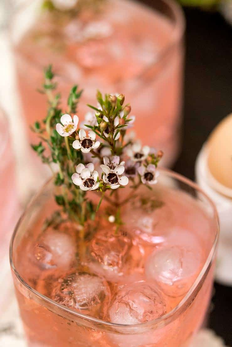 A closeup of small flowers and thyme in a pink cocktail, in front of 2 de-focused cocktails.