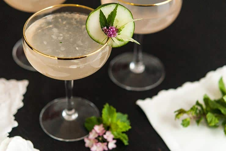 A cocktail with a cucumber and flower garnish on a black table beside 2 other cocktails. There are flowers, a small bunch of mint and antique napkins on the table.