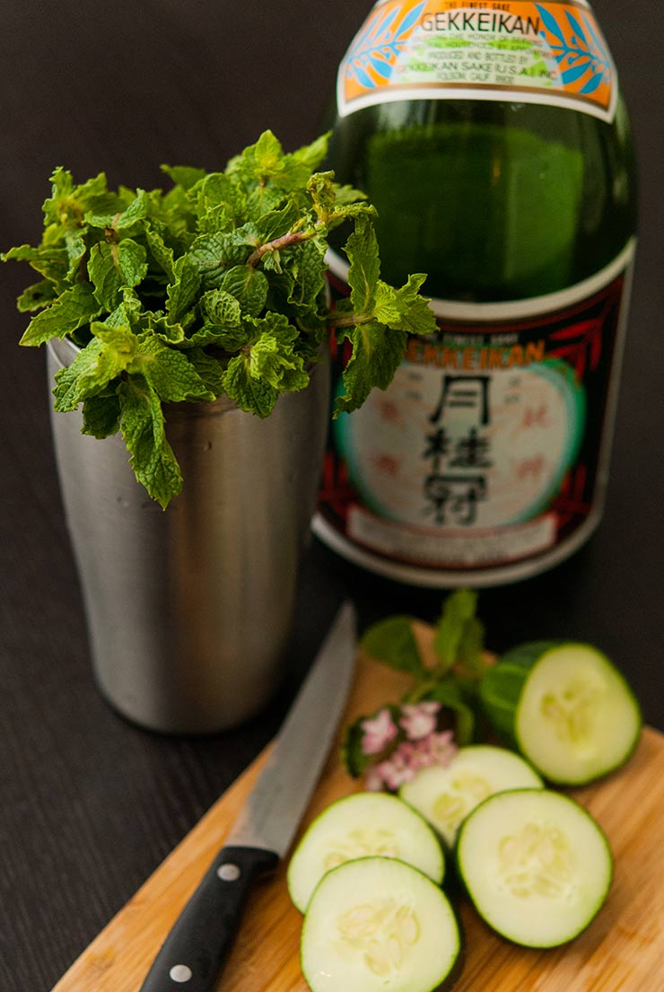 A cocktail shaker full of mint next to a bottle of sake. A cutting board with sliced cucumbers in in front.