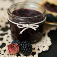 A small jar of jam, tied with a string bow on a lace table cloth, and 2 berries in front of it.