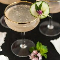 A cocktail garnished with cucumber, a leaf and flower with 2 other glasses in the background and napkins on the table.
