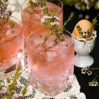 3 pink cocktails, garnished with flowers and rosemary on a lace cloth, beside an egg in an egg cup, tied with flowers.