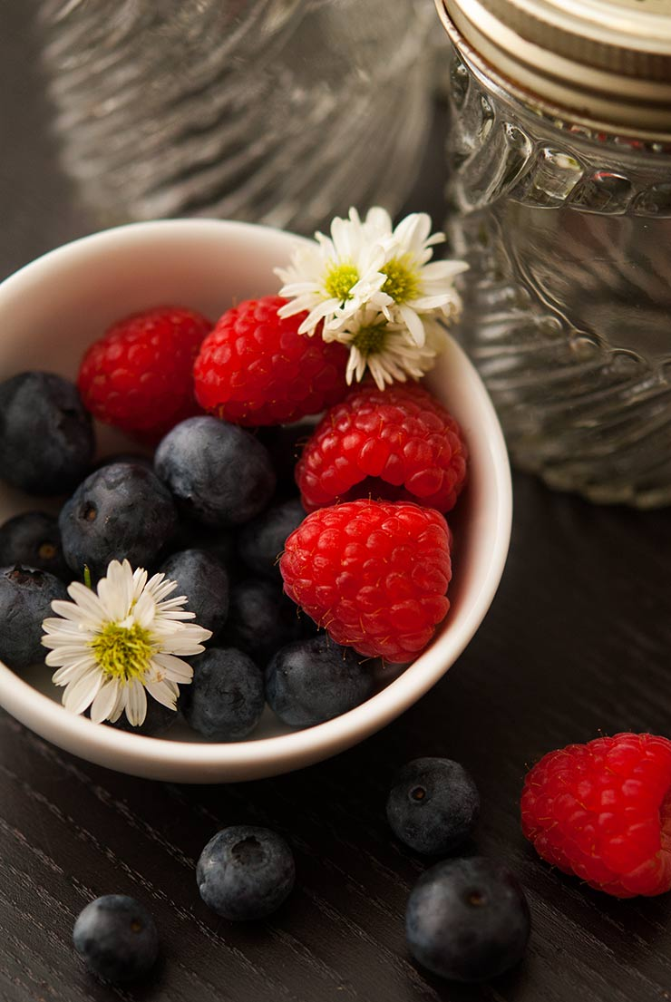 A small white bowl full of raspberries, blueberries and small daisies on a black table.