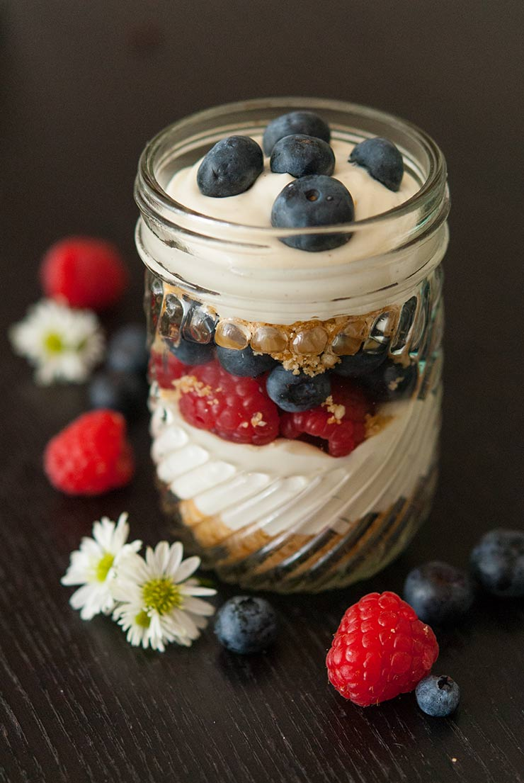 A mason jar with layered cheesecake mouse, cookie crumbles and berries on a black table.