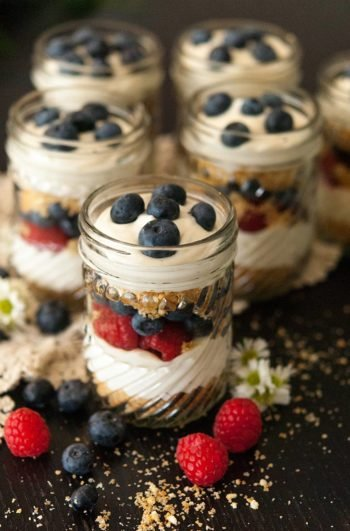 6 mason jars with layered cheesecake mouse, cookie crumbles and berries on a black table, sprinkled with cookie crumbs and berries.