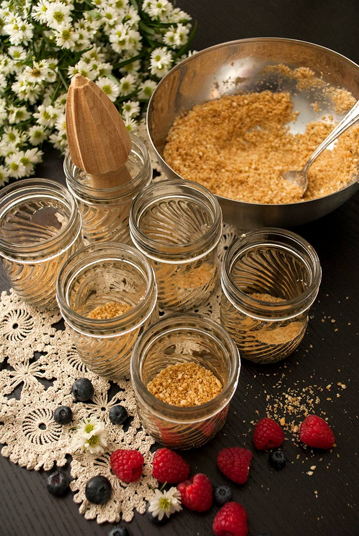 6 mason jars with cookie crumbles on the bottom on top of a lace cloth beside a bowl of cookie crumbles and a bouquet of daisies.